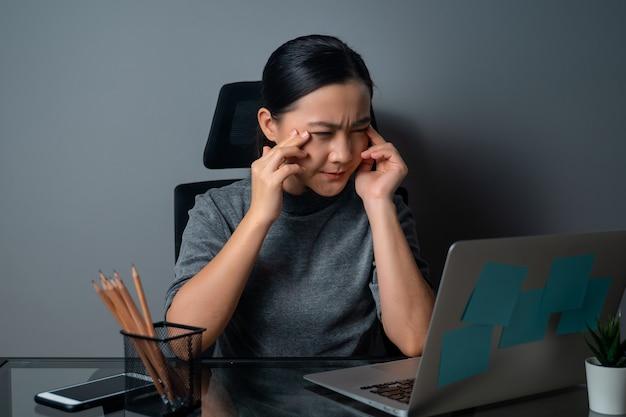 아시아 여자는 눈의 통증으로 아팠고, 그녀의 눈을 만지고, 사무실에서 노트북으로 작업했습니다.