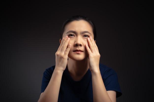 Азиатская женщина болела с болью в глазах, раздражала зуд в глазах, изолированные на фоне.