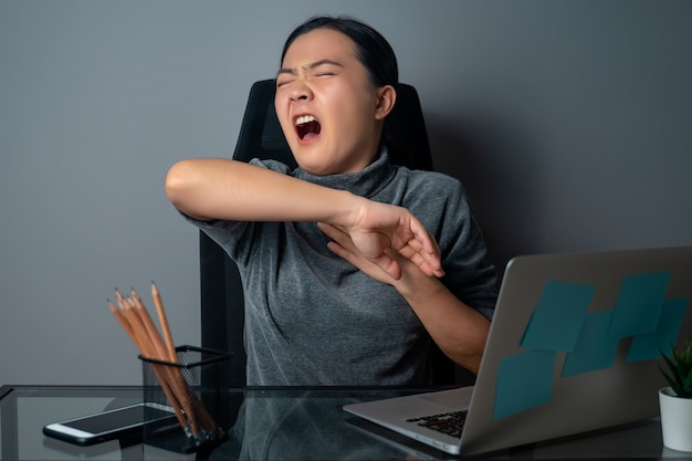 Asian woman was sick with fever, working on a laptop at office