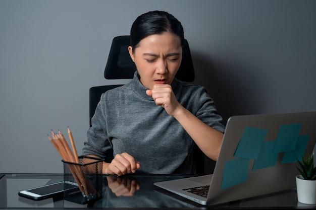 アジアの女性は、オフィスでラップトップに取り組んで、熱にうんざりしていました