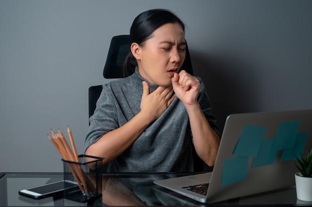 Азиатская женщина заболела лихорадкой, работая на ноутбуке в офисе