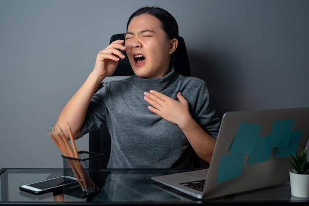 아시아 여성은 열이 나고 사무실에서 노트북으로 작업했습니다.