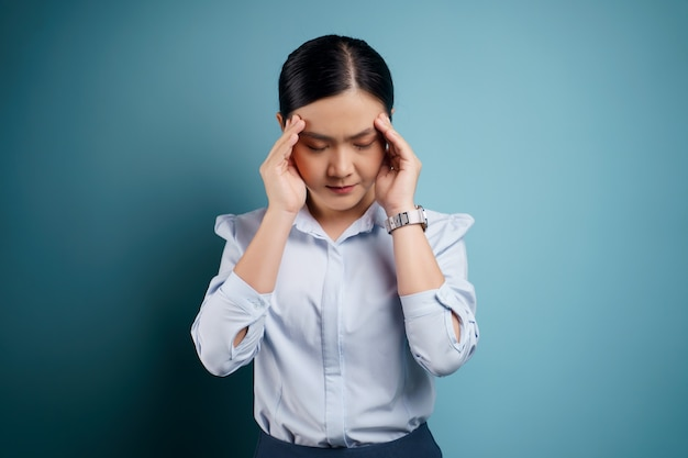 Asian woman was sick with headache touching her head isolated on blue.