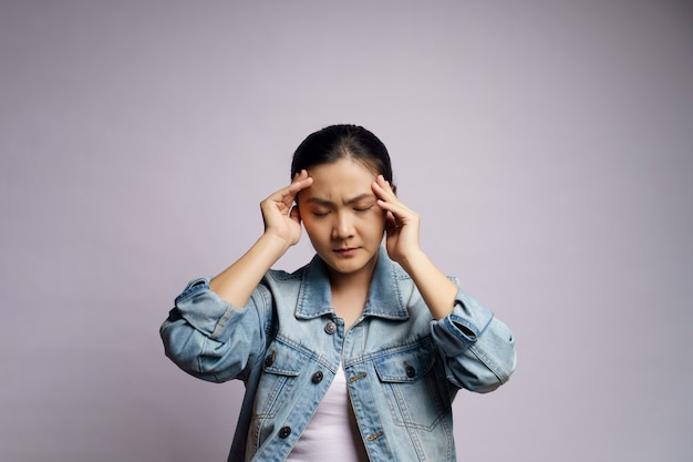 Asian woman was sick with headache touching her head isolated.