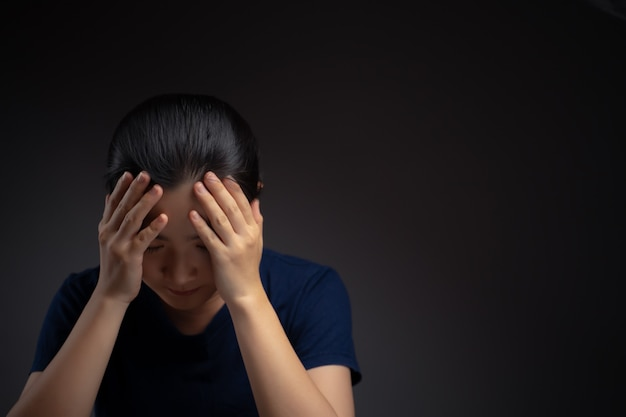 Asian woman was sick with headache touching her head standing isolated on background.