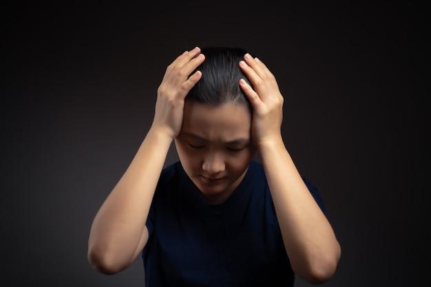 アジアの女性は、背景に孤立して立っている彼女の頭に触れる頭痛で病気でした。
