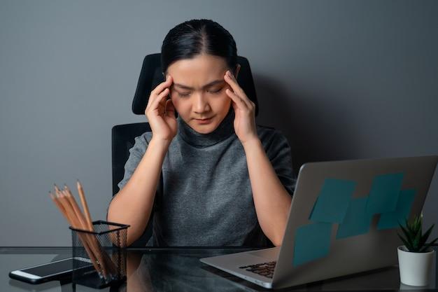 아시아 여자는 두통으로 아팠고, 그녀의 머리를 만지고, 사무실에서 랩톱에서 작업했습니다.