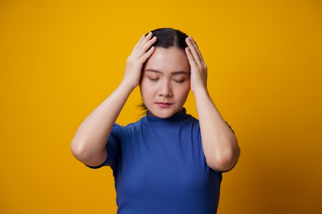 Asian woman was sick with headache touching her head on yellow.