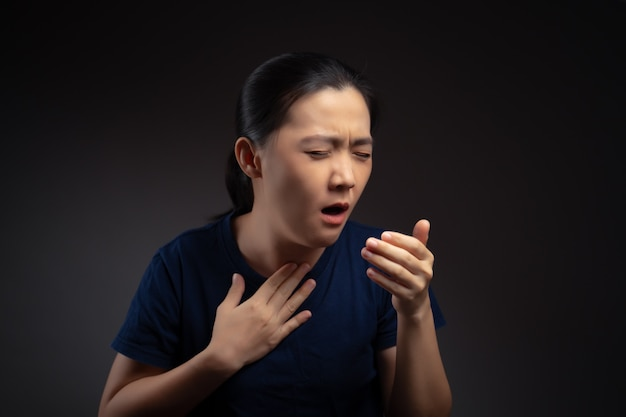 Asian woman was sick with sore throat, coughing and sneezing isolated on background.