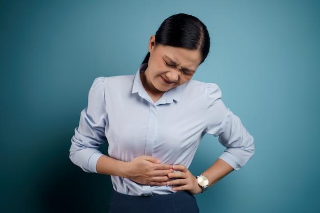 아시아 여성은 복부를 눌러 손을 잡고 복통으로 아팠습니다.