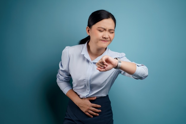 Asian woman was sick with stomach ache holding hands pressing her abdomen