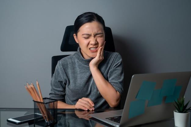 아시아 여자는 사무실에서 그녀의 뺨을 만지고 치통으로 아팠다.
