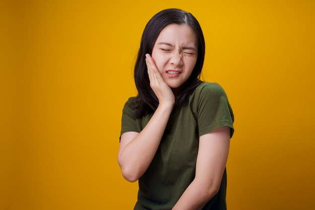Asian woman was sick with toothache touching her cheek and standing isolated on wall.