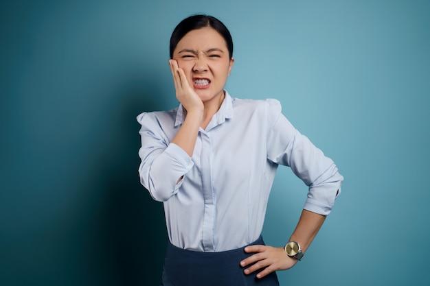아시아 여자는 그녀의 뺨을 만지고 치통으로 아팠다. 프리미엄 사진