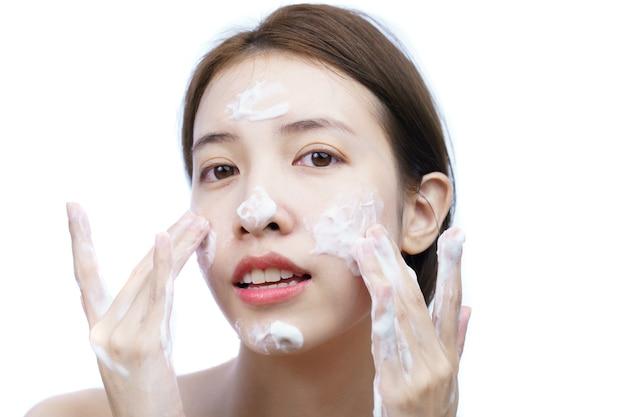 아시아 여자는 고립 된 거품 클렌징 거품으로 그녀의 얼굴을 씻어