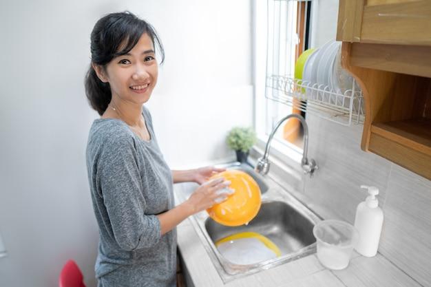 부엌에서 설거지하는 아시아 여자