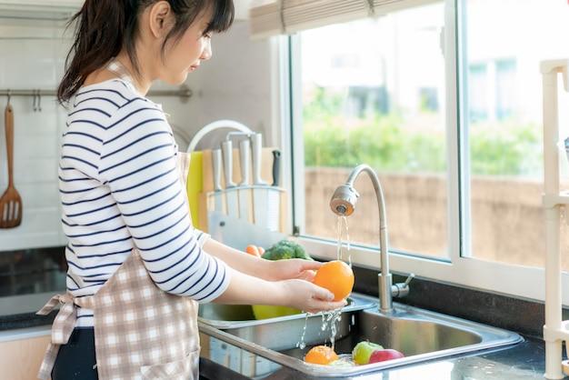 アジアの女性が台所で野菜を洗う