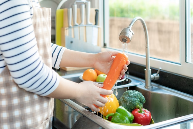 Asian woman washing vegetables in the kitchen