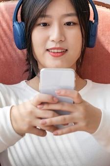 Азиатская женщина смотрит видеоклип с телефона