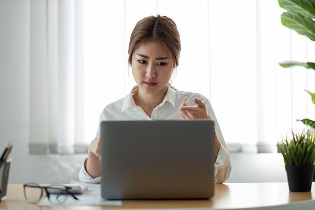 노트북으로 교육 웨비나를 보고 있는 아시아 여성. 고객 파트너와 화상 통화를 들고 웃는 젊은 사업가.