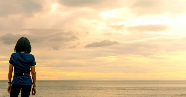 海のビーチで日の出の空を見ているアジアの女性。ランナーは、熱帯のビーチで実行した後リラックスします。健康的な生活様式。女の子は夏休みに一人で旅行します。海の海岸での休日。