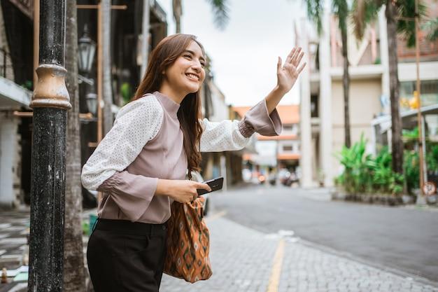 タクシーを待っている間、アジアの女性が手を振る