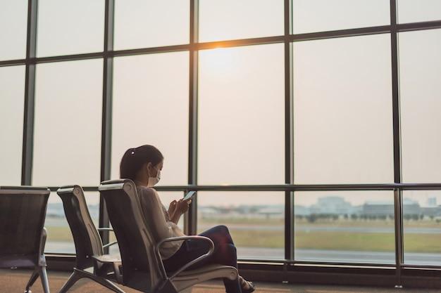 アジアの女性は、空港ターミナルのバックグラウンドでフェイスマスクを着用し、スマートフォンを使用しています。公共交通機関の概念covid 19.とコロナウイルス、社会的距離の発生時に注意深く。