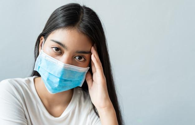 フェイスマスクを着用したアジア人女性は、頭痛のために頭を抱えています。ストレスや睡眠不足、睡眠不足、コピースペースのある健康的なコンセプトでの休息不足のため、発熱と片頭痛があります。