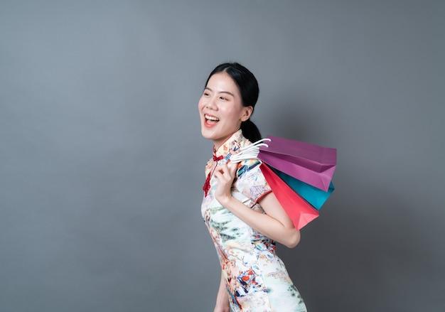アジアの女性は灰色の表面に買い物袋を持っている手で中国の伝統的な衣装を着ています