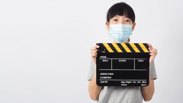 아시아 여성은 흰색 배경의 비디오 제작, 영화, 영화, 영화 산업에서 얼굴 마스크와 손을 잡고 검은색 클래퍼 보드 또는 영화 슬레이트 또는 클랩보드를 사용합니다.