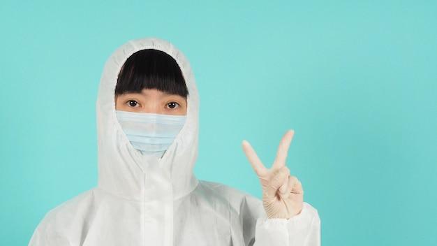 아시아 여성은 민트 그린이나 티파니 블루 배경에서 승리의 손이나 평화 사인을 하는 얼굴 마스크와 ppe 슈트를 착용합니다.