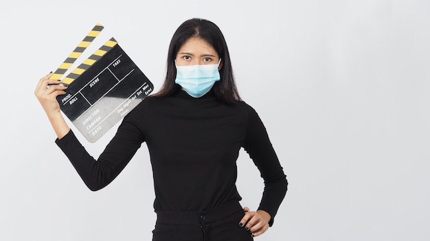 Asian woman wear face mask and hand's holding black clapper board or movie slate use in video production ,film, cinema industry on white background.