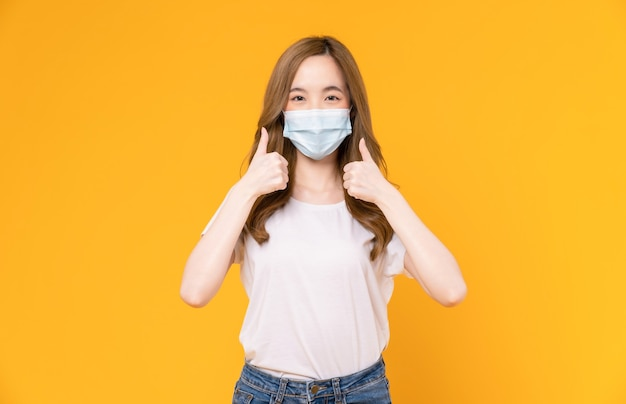 Asian woman wear masks to protect disease and showing thumbs up or like on yellow background.