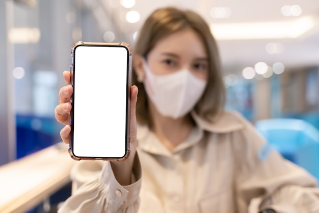 아시아 여자는 공항 터미널에서 여행하는 동안 흰색 화면 모바일 모형을 보여주는 마스크를 착용합니다.
