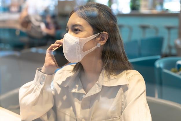 アジアの女性が空港ターミナルで旅行中にスマートフォンで話しているマスクを着用
