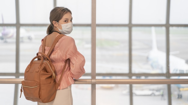 Asian woman wear masks while traveling at the airport terminal. new normal, covid19 disease prevention  concept.