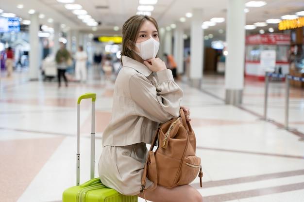 아시아 여자는 공항 터미널에서 여행하는 동안 마스크를 착용합니다. 새로운 정상, covid19 질병 예방 개념.