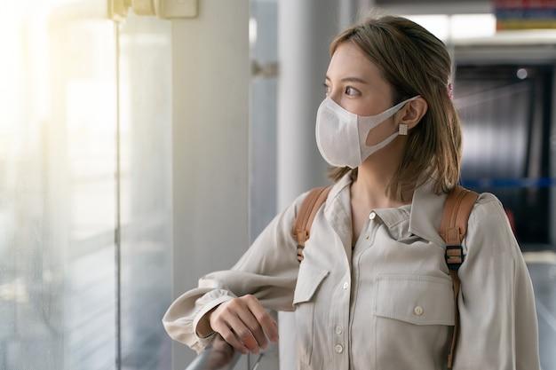 空港ターミナルで旅行中にアジアの女性がマスクを着用