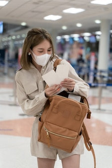 Asian woman wear masks while traveling, holding boarding pass at the airport terminal. new normal, covid19 disease prevention concept.