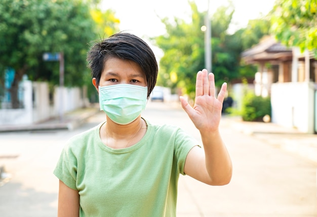 Asian woman wear medical mask show stop sign hand for corona, covid 19 virus outbreak or pm 2.5 air pollution. corona virus, covid 19 virus outbreak, medical mask or virus outbreak concept