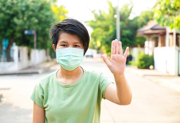 아시아 여성은 코로나, covid 19 바이러스 발생 또는 pm 2.5 대기 오염에 대한 의료 마스크 쇼 정지 신호를 착용합니다. 코로나 바이러스, covid 19 바이러스 발생, 의료 마스크 또는 바이러스 발생 개념