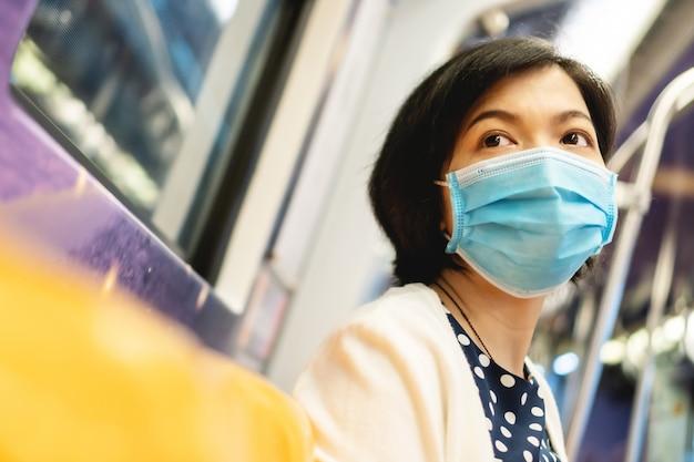 アジアの女性は、地下鉄通勤で保護フェイスマスクを着用します。