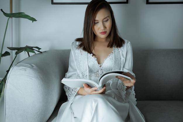 아시아 여자는 잠들기 전에 밤에 회색 소파에 잡지 기사를 읽고 꽃 레이스와 흰색 잠옷 & 긴 소매 새틴 가운을 착용하십시오.