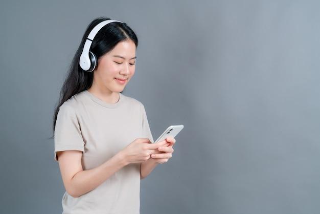 아시아 여자 착용 무선 헤드폰 보류 스마트 폰 음악 앱을 사용하여 전화 화면을보고