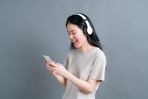 Asian woman wear wireless headphone hold smartphone looking at phone screen using mobile player app listening online music, learning foreign language, watching video relaxing on grey wall