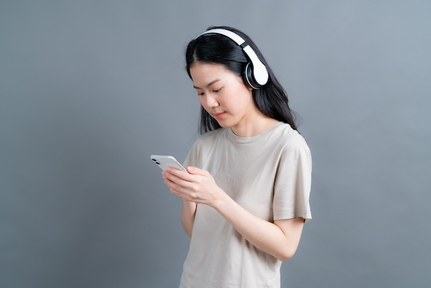 Asian woman wear wireless headphone hold smartphone looking at phone screen using mobile player app listening online music, learning foreign language, watching video relaxing
