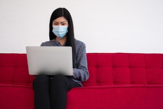 Азиатская женщина нося лицевой щиток гермошлема и используя компьтер-книжку на софе для работы от дома.