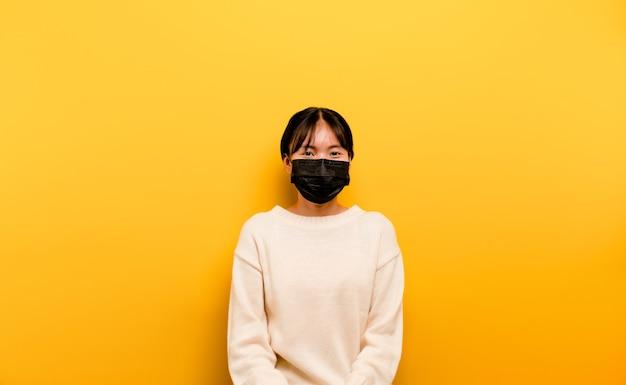 Азиатская женщина в маске профилактика вируса короны отдых в карантине концепция социальной и эмоциональной дистанции, о которой вы думаете. девушка в медицинской маске желтая сцена студийная фотосъемка