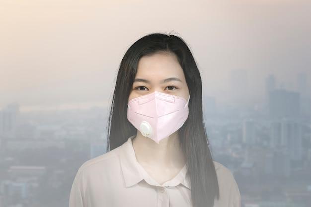 오염된 도시에서 마스크를 쓴 아시아 여성