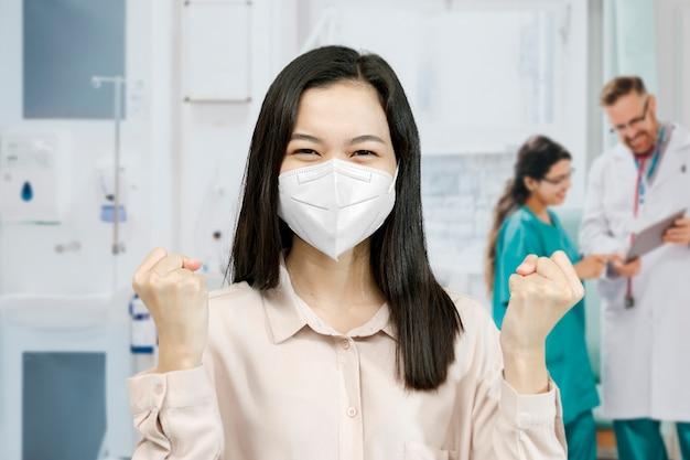 병원에서 손을 들고 마스크를 쓴 아시아 여성